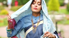 Woman in blue sari and jewelery tying head with lace scarf. Stock Footage