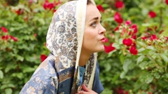 Woman folding her hands in prayer among rose bushes in park. Stock Footage