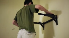 Man getting on horizontal bar on wall and on hands raising legs. Stock Footage