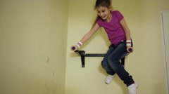 Girl smiling and hanging by hand on wall horizontal bar. Stock Footage