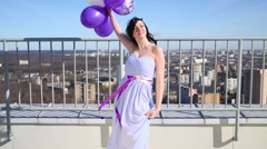 Girl brunette posing with white and purple air balloons on roof. Stock Footage