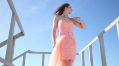 Woman throwing up hands and touching dress next to handrail on roof Stock Footage