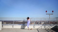 Woman climbing fence on roof with ball, picking it up Stock Footage