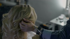 In a beauty salon eccentric stylist makes professional styling for the girls Stock Footage