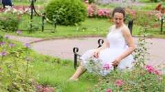 Woman in white dress touching flower bed of roses on grass in park. Stock Footage