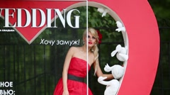 Woman in dress peeping out from large cover of magazine wedding Stock Footage