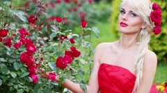 Blonde in red dress is smelling rose flowers, sitting next to bush. Stock Footage