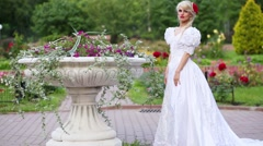 Woman is going out of flowerbed with flowers in park, holding long skirt. Stock Footage