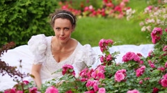 Brunette woman sitting on grass among roses and smelling flower bud. Stock Footage