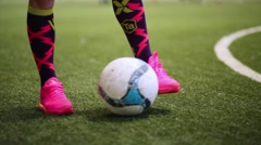 Female feet pushing ball on green court for game of football. Stock Footage