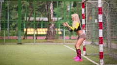 Blonde standing at gate in mini soccer field catching ball Stock Footage