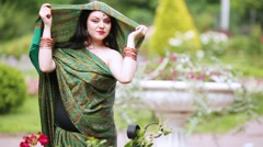 Woman in sari dressing her on head and turning in front of flowerbeds Stock Footage