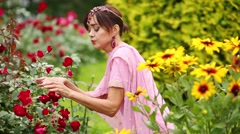 Woman in pink sari sitting in flowers and touching and smelling roses Stock Footage