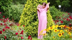 Woman in pink sari among flowers touching branches arborvitae. Stock Footage