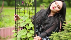 Black-haired woman posing in lattice rack with climbing plants Stock Footage