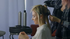 Stock Video Footage of in a beauty salon eccentric stylist makes professional styling for the girls