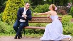Woman in dress pulling hands to man on park bench. Stock Footage