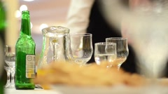Glass of drink and beer bottle at a table where people sit and tell - stock footage