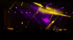 Musical band singing on stage colored spotlight in front of numerous fans ass - stock footage
