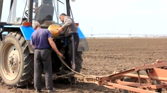 Two farmers filled the tractor with diesel fuel Stock Footage