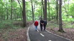 Older men and young cyclists walking on a paved path through the thick forest Stock Footage