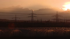 Industrial landscape with electrical towers and greenhouses and sunset Stock Footage