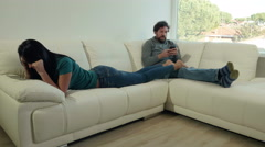 Young couple relaxing at home on sofa with technology texting and playing wit Stock Footage