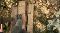 A man walking on small wooden bridge over river in forest. Slow motion Stock Footage