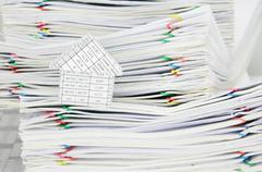 House and overload of paperwork with colorful paperclip - stock photo