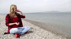 Girl sitting on the beach. Girl and sea. Joy, carefree, recreation. Rocky beach. Stock Footage