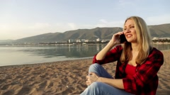 Woman talking on the phone at the beach. Cellular. Mobile phone. - stock footage