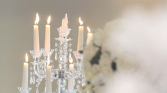 Burning candle on a candlestick and flowers in the foreground with blur - stock footage
