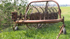 Abandoned rusty hay rake - agricultural machine - in a grassy field. 4K zoom. Stock Footage