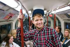 Young hipster man standing in a crowded subway train Stock Photos