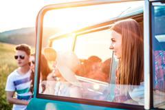 Group of teenage hipsters on a roadtrip, campervan Kuvituskuvat