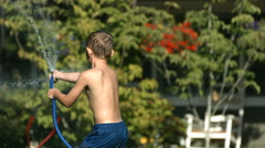 Kid spraying water from hose, slow motion Stock Footage