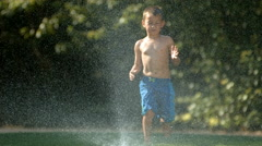 Kid jumping over sprinkler, slow motion Stock Footage
