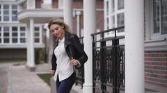 The blonde in a black leather jacket, smiling, to her a little bit cool. Around Stock Footage