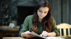 Pretty girl reading menu in the cafe and smiling to the camera Stock Footage