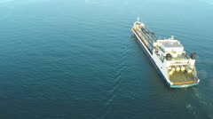 AERIAL, trade ship leaving the harbor at the sunset time going to open ocean. Stock Footage