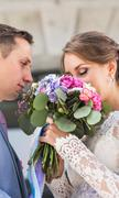 wedding couple hugging, the bride holding a bouquet of flowers,  groom embracing - stock photo