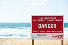 Red danger sign on an ocean beach with waves on the background Stock Photos