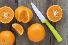 Mandarin oranges and acrylic knife placed on the old wooden floor. Stock Photos