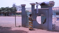 Local woman entering the school gate, Ghana Stock Footage