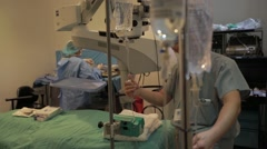 Surgical assistant adjusting iv drip in operation theatre Stock Footage