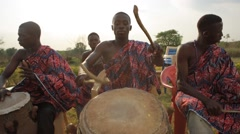 Tribes playing drum in field, Ghana Stock Footage