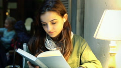 Girl listening music on earphones and reading book in the cafe Stock Footage