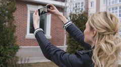 Side portrait of a beautiful blond girl using a smart phone to network, taking Stock Footage