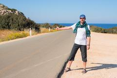 Man with backpack travels hitchhiking - stock photo