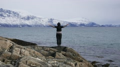 A person stands and meditates on the shore of the fjord. Stock Footage